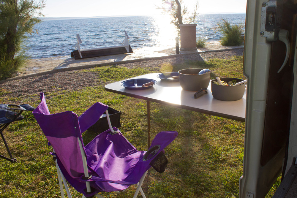 Camping table and chairs outside van door with view over water. Easy van rental in Iceland is flexible.