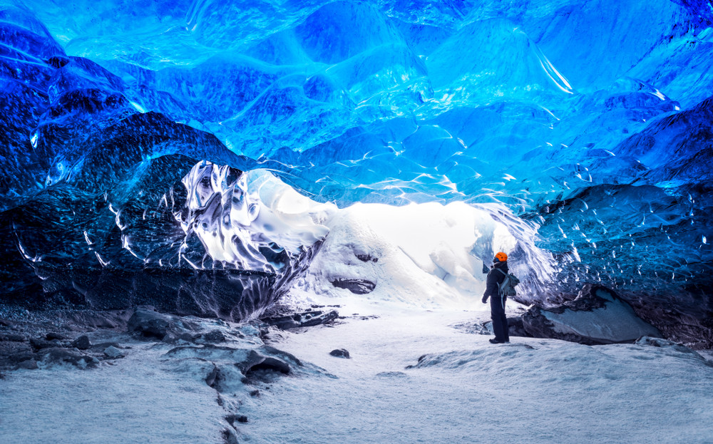Person in winter gear looking up inside a glittering blue ice cave. Winter activities in Iceland