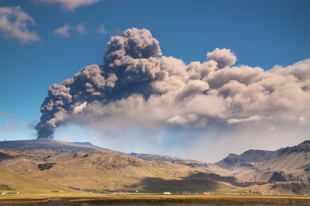Large clouds of dense smoke erupting from a volcano into blue skies. Active volcanoes of Iceland.