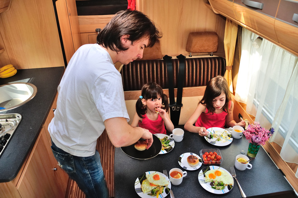 View inside a motorhome. Two young girls sit eating at a table while a man serves food. Travelling with kids in Iceland.