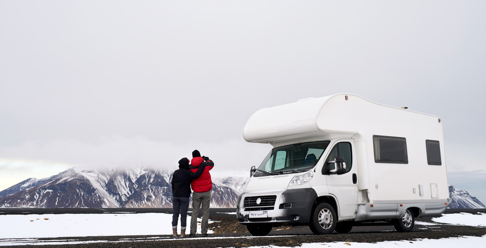A couple stand next to a motorhome enjoying a snowy mountain view. How to find the best camper rental in Iceland