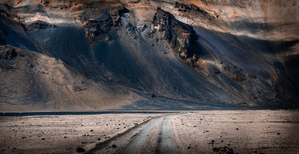 Volcanic landscape in Iceland highlands with a gravel road. Driving safely in Iceland means going slow and steady.