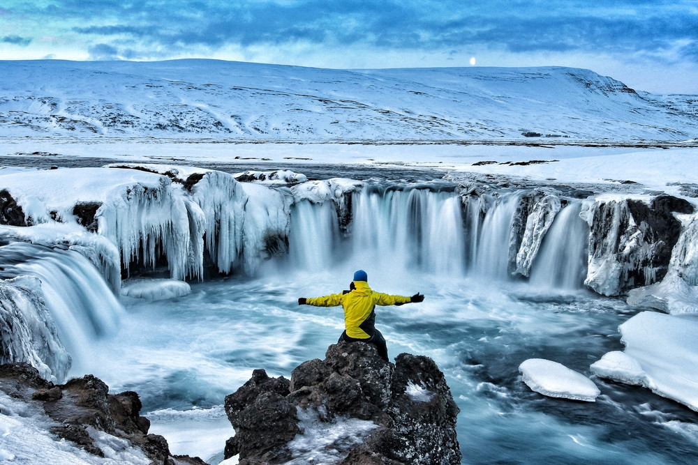 Man with outstretched arms sitting on a rock overlooking a huge waterfall. Partly frozen with snowy views. Camping and caravanning in Iceland in winter!