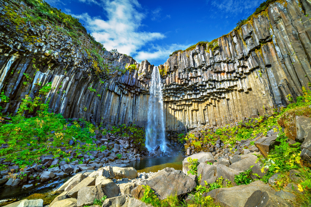 A long thin waterfall surrounded in columns of rock. Blue skies and greenery. Self-drive road trips in Iceland.