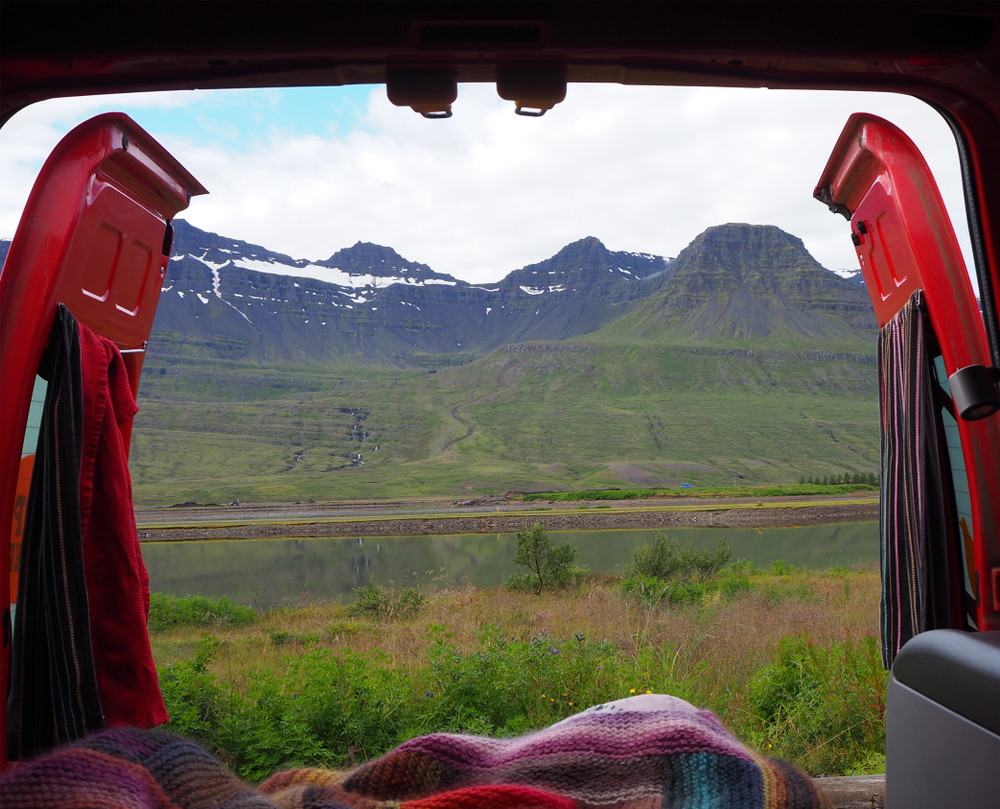 View from the back of a camper van out across a green landscape. Camping is a great way to see Iceland on a budget