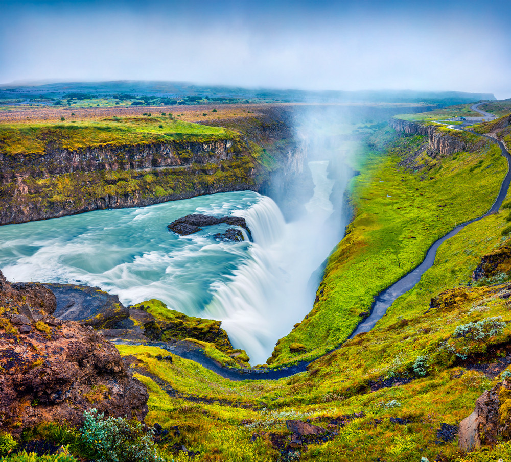 Water rushing down into a long river gorge amidst green hills. One of the most beautiful waterfalls in Iceland, Gullfoss Waterfall