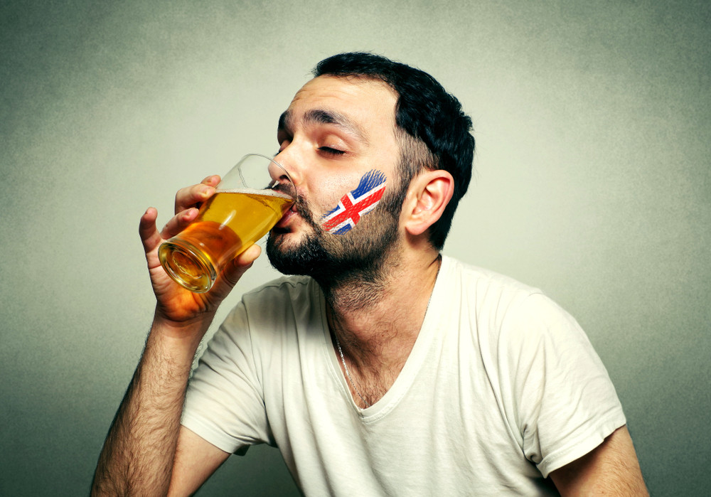 Man drinking a glass of Icelandic beer with the Iceland flag painted on his face.