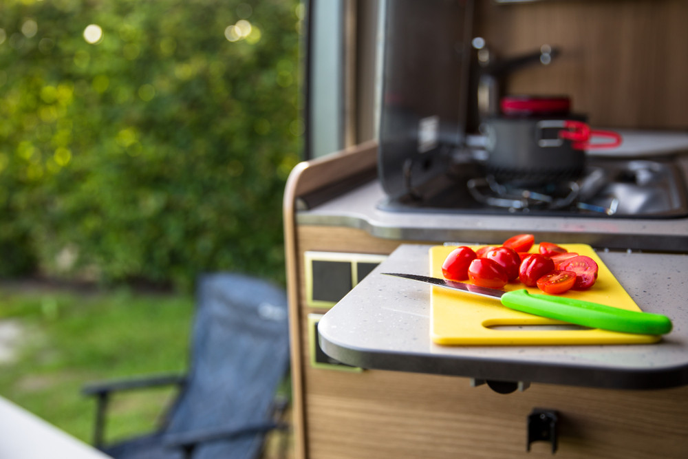 Motorhome kitchen view of tomatoes on chopping board. Advantages of driving a motorhome in Iceland