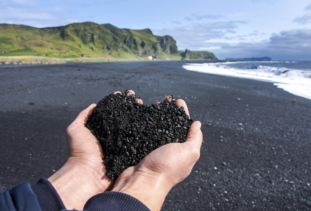 Two hands cradling black sand in a heart shape. View of the beach and sea. Iceland honeymoon ideas.