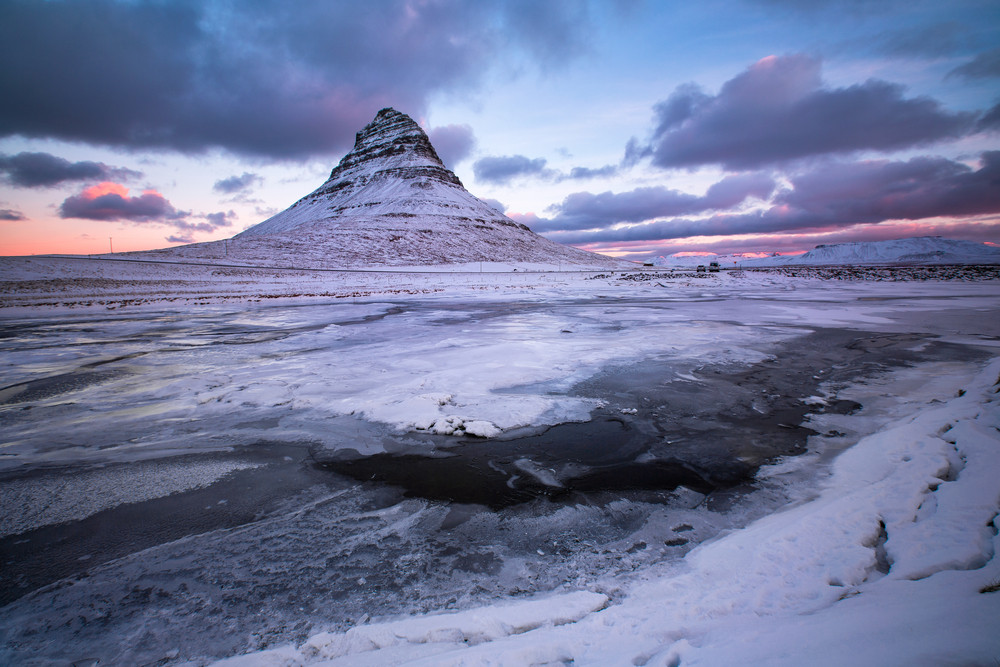 An icy scene under a twilight sky with a distinctive painted mountain rising up. The Kirkjufell Mountain is a dramatic Game of Thrones filming locations in Iceland