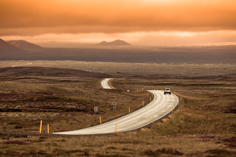 A long road winds through a remote landscape. Tonal oranges and mauve sunset. Driving the Iceland ring road.