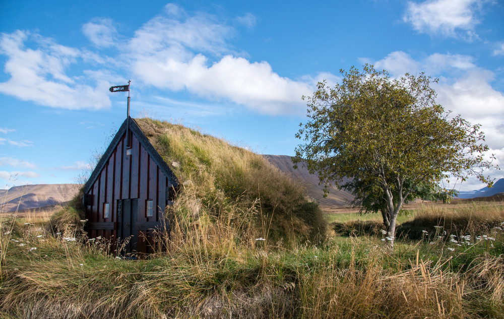 One of the early turf roof churches in Iceland. Wooden frame with turf roof and meadows surrounding it under blue skies.