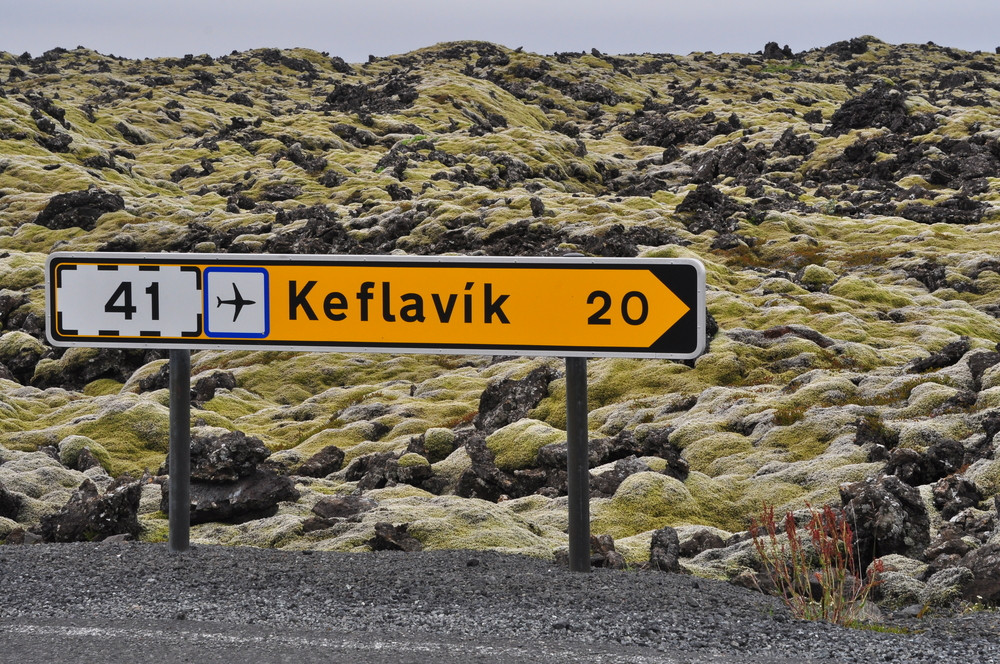 Signpost in volcanic landscape. Keflavik shuttle bus service runs to the capital.