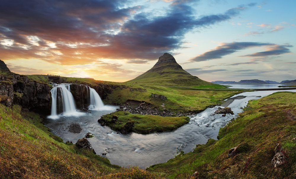 Beautiful scene of a waterfall cascading into a pool, green surrounding meadow and a rounded mountain peak behind. Taken on the Snaefellsnes Peninsula, Iceland