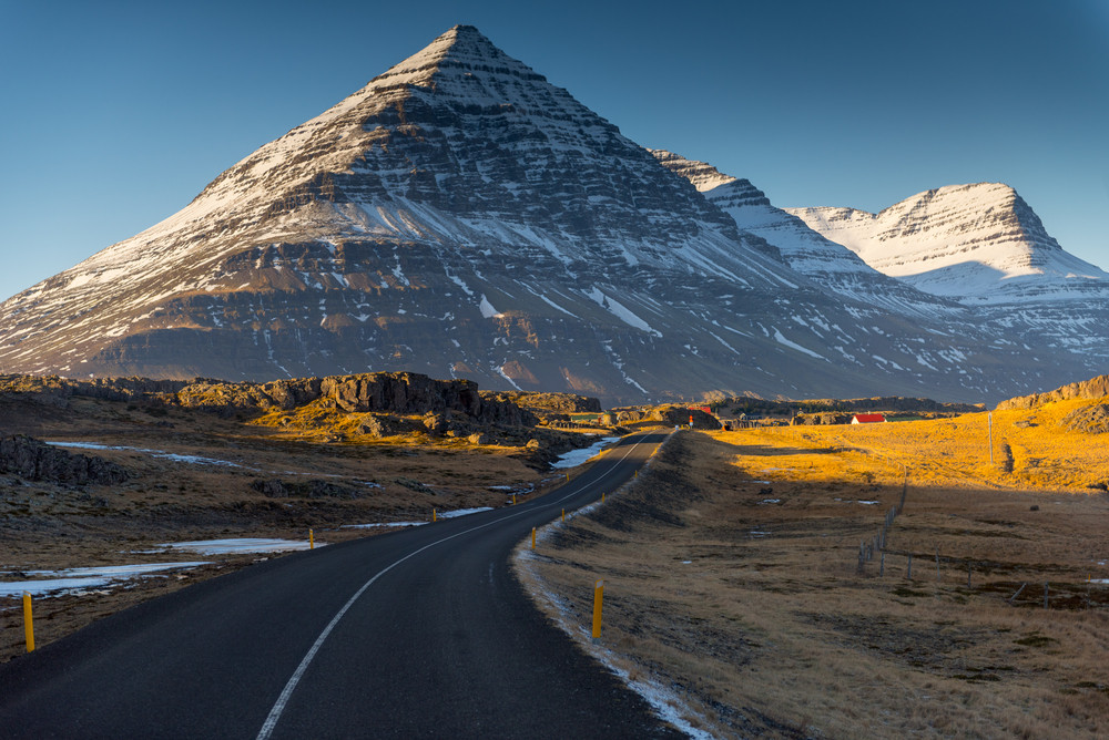 Spring in Iceland landscape - sun and snow and a road leading up to a mountain.