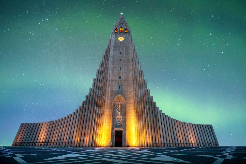 Hallgrímskirkja Church at night. Striking modernist structure lit up in orange light with the green of the Northern Lights behind. One of the most beautiful churches in Iceland.
