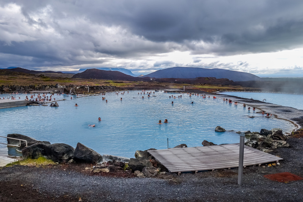 wide open blue pool with people bathing. Steam rises and there are mountains and a moody sky. Lake Myvatn Nature Baths close to the Iceland Ring Road.