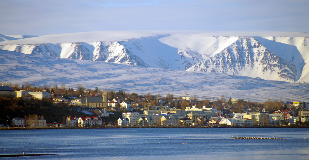 View from the water of Akureyri one of the northern cities in Iceland. Snowy mountains back the city.