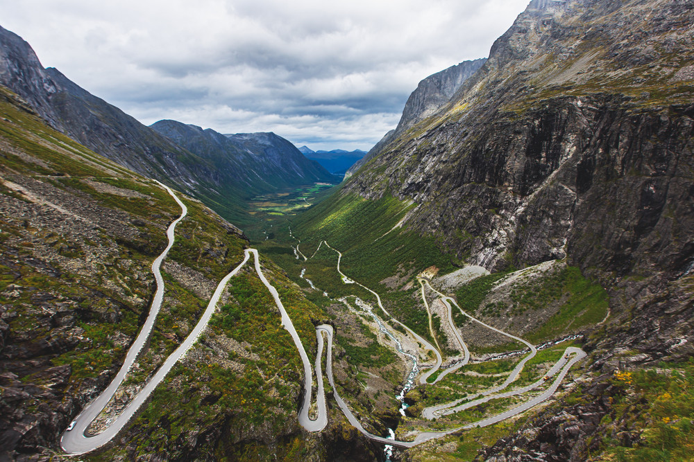 zig-zag roads though a valley with steep sided mountains. Trolls in Iceland.