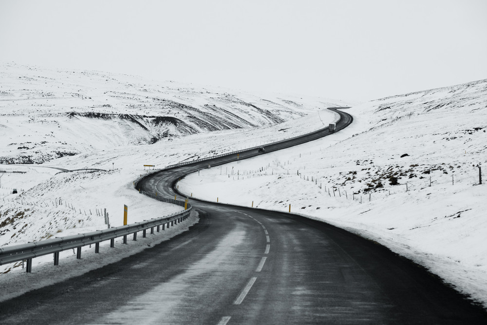 A grey road winds uphill through a snowy landscape. The Iceland weather and climate is harsh in winter.