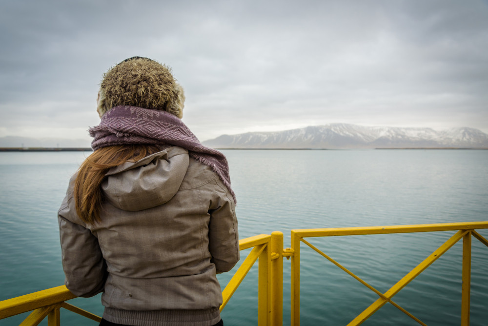 Girl wrapped up warm at edge of boat barrier looking out at snowy mountains. Reykjavik Old Harbor.