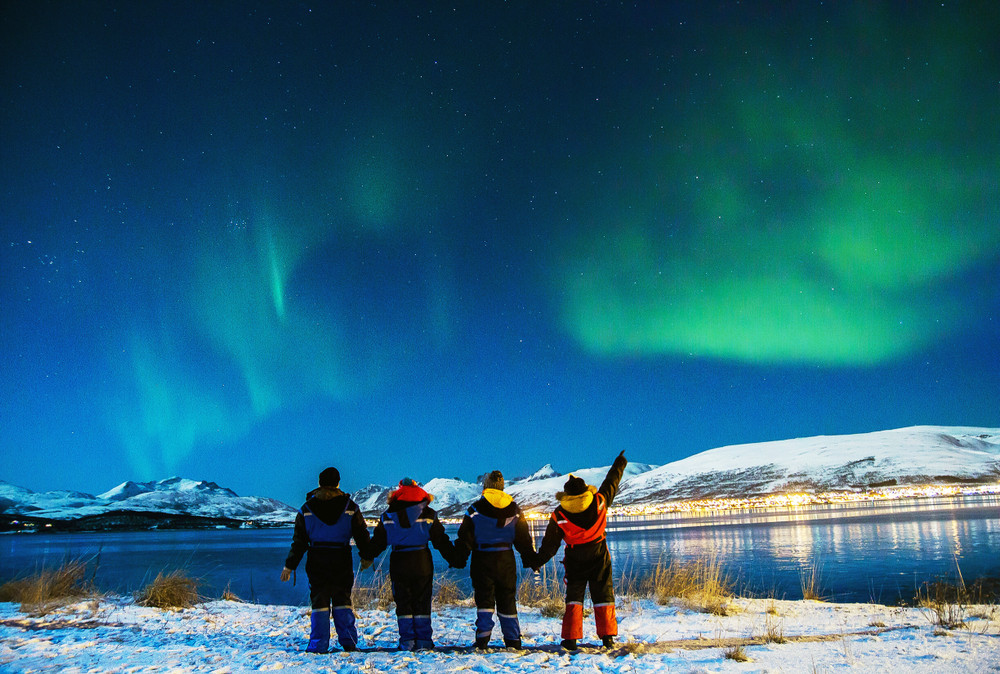 Four people in snow gear stand and watch the Northern Lights over a lake. Snowy landscape. Travelling with Kids in Iceland.