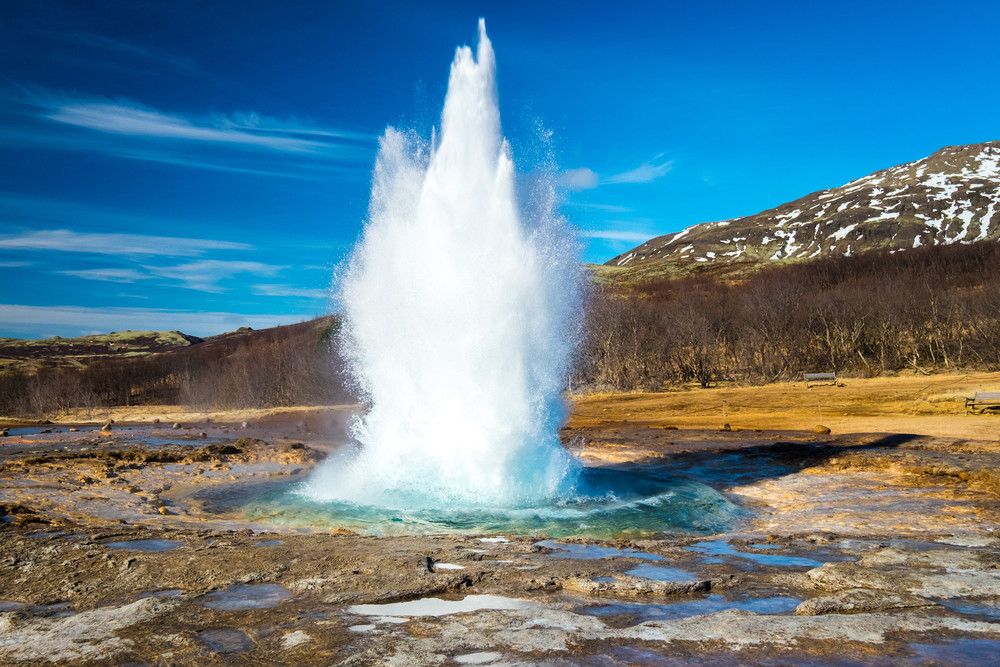 Water jetting out of a geyser under blue skies. It is free to visit the Geyser National Park, Iceland on a budget.