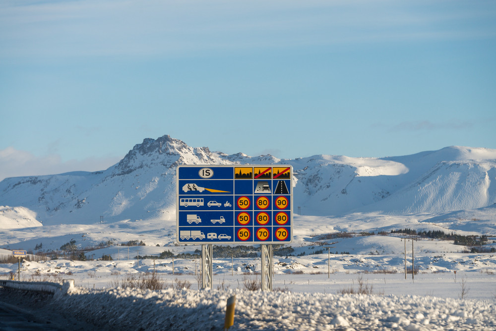Road sign to help with driving safely in Iceland. Snowy landscape background.
