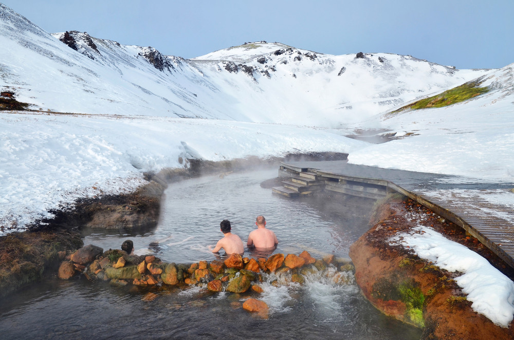 Three men in hot spring river pool with snowy hills around. Iceland camper van in winter.