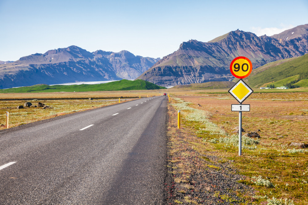 An Iceland speed limit sign of 90 on the side of an empty rural road with mountains in the distance.