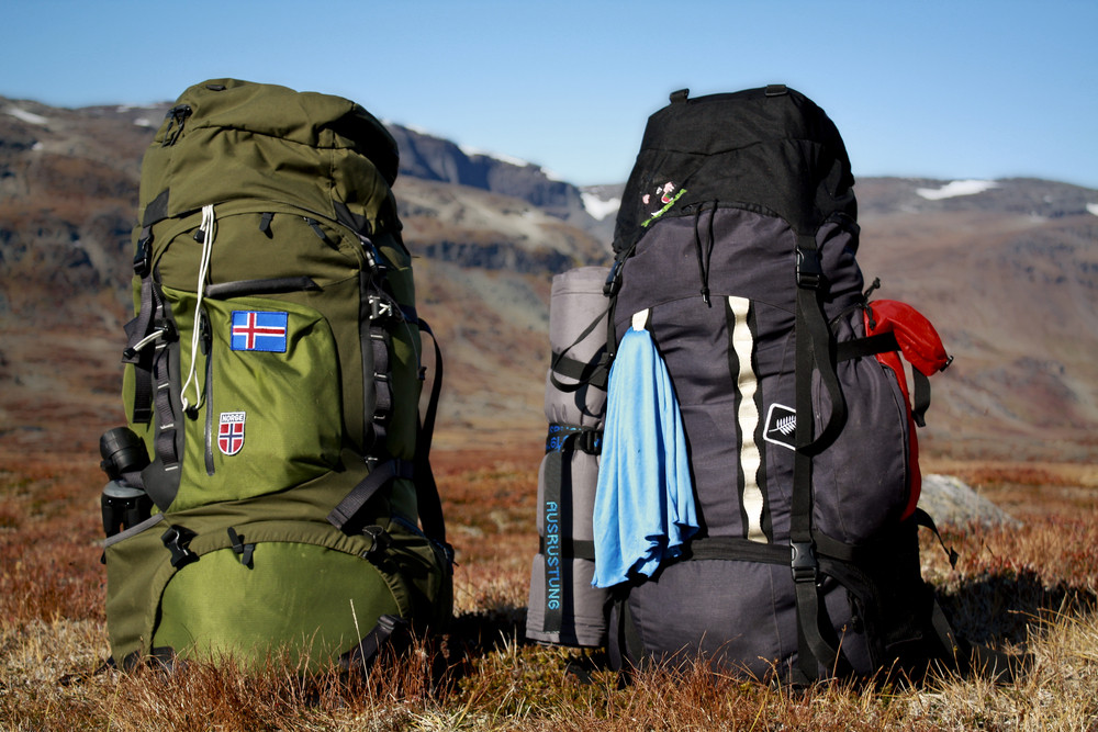 Two rucksacks side by side in a field. Campsites in Iceland.