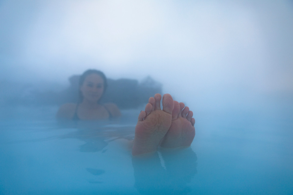 Woman relaxing in a steamy pool with feet up. Reykjavik city card includes entry to thermal pools.