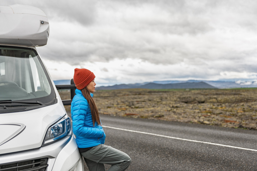 Young woman in warm gear leans on parked motorhome. Special license to drive a motorhome in Iceland?