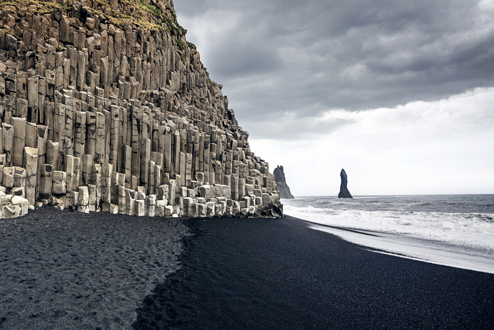 One of the striking Iceland beaches with black sand and basalt columns. Stormy sky and black rock sea stacks.