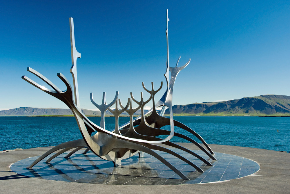 Sun Voyager sculpture inspired by Islendingur Viking Ship. Blue skies and ocean in background.