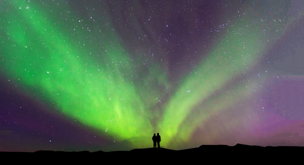 Starry sky and green Northern Lights. Couple stand and stare in the distance.  Iceland in October.