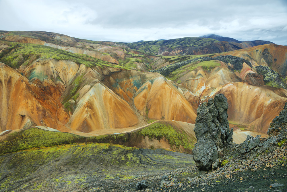 Colourful mountain scene with black, green and shades of rust orange and browns. The Fjallabak Nature Reserve is home to one of the nicest pools and hot springs in Iceland. The  Landmannalaugar Hot Pot