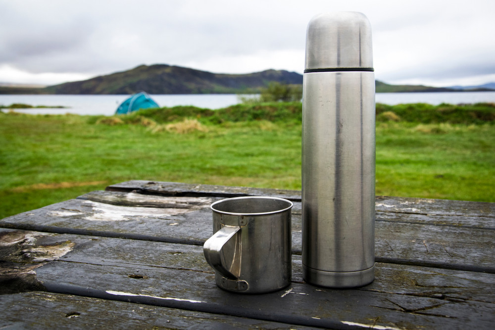 Thermos and cup on picnic table overlooking lake and tent. Right to roam in Iceland.