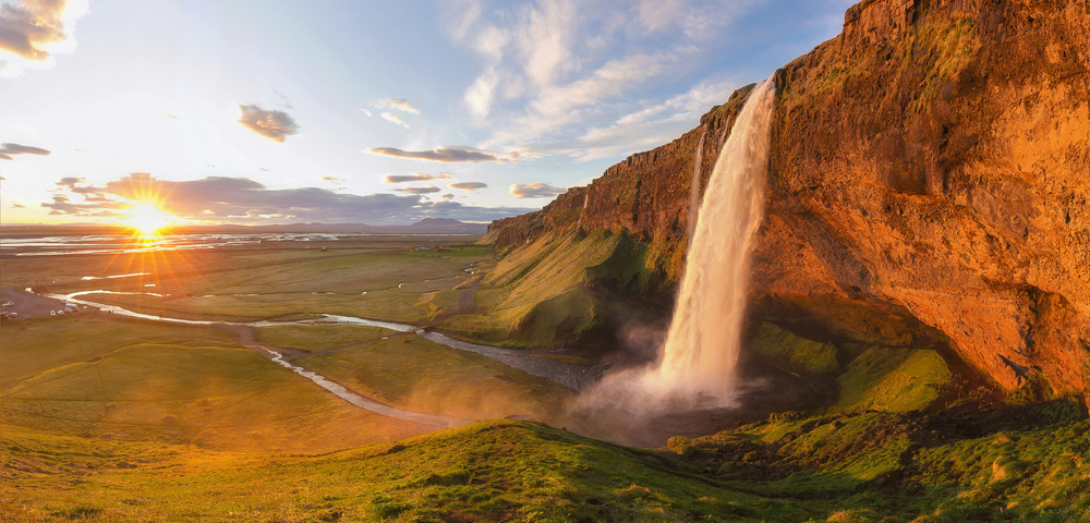 Beautiful waterfall and low sunlight over green fields. Spring in Iceland.
