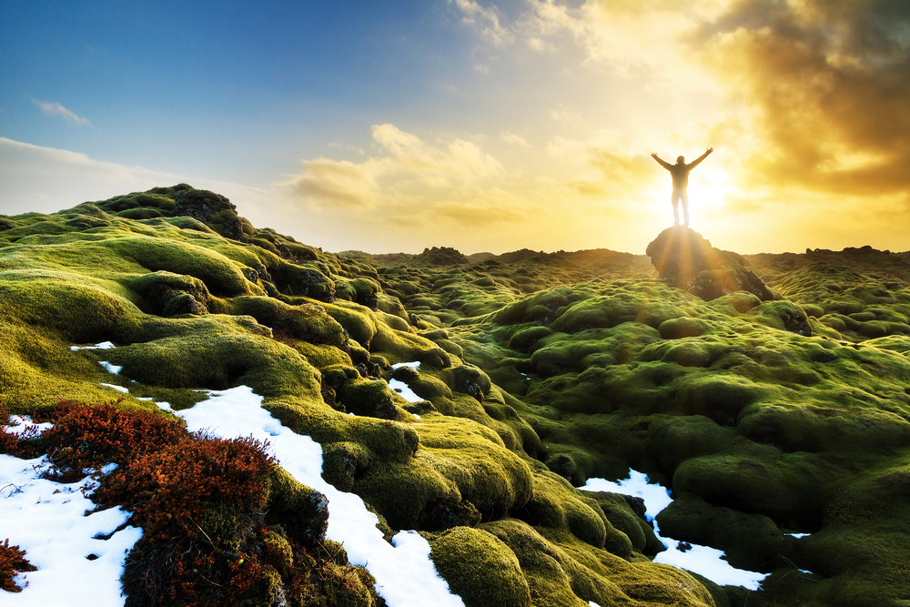 Beautiful mossy landscape at sundown. Person standing arms outstretched on distant rock. Solo travel in Iceland.