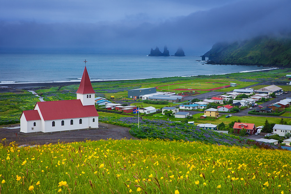 One of the most picturesque churches in Iceland. Red and white overlooking the town and dramatic coast with dark rock formations. Stormy sky contrasts with yellow flowers in foreground.