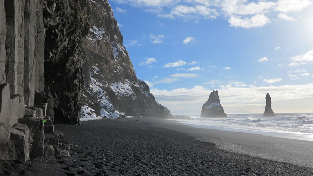 View of a black sand beach looking out to sea. Steep black column cliffs and two columns visible out at sea. Reynisfjara Black Sand Beach is one of the highlights of South Iceland