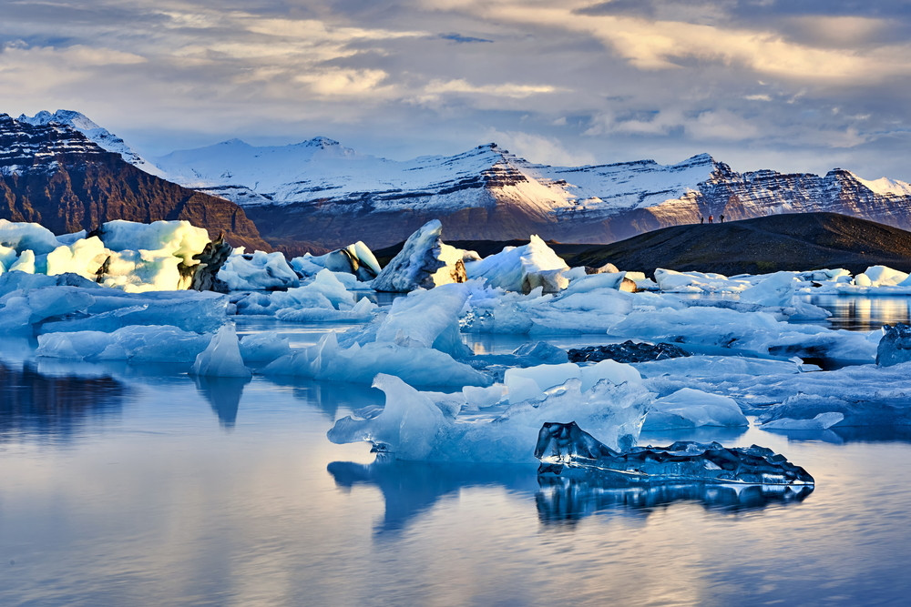 Light catching the ice floating on a lake with snowy mountains behind. Jokulsarlon Glacier Lagoon Iceland.