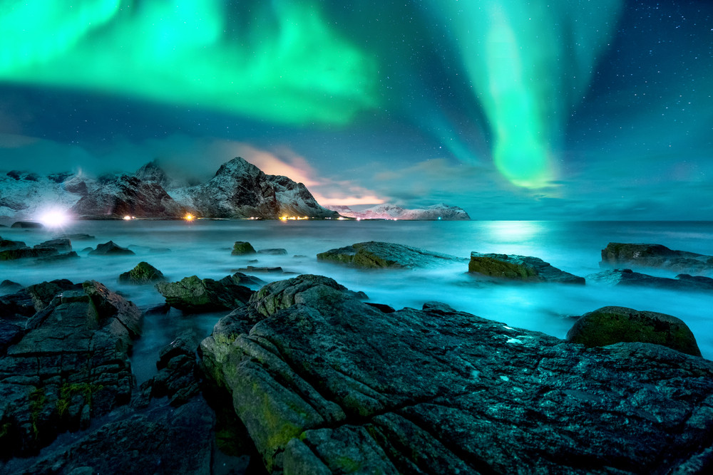 Night view over shoreline, islands and ocean. Blue and green Northern Lights reflect in water and a pink glow on the horizon. Find the Northern Lights in Iceland.