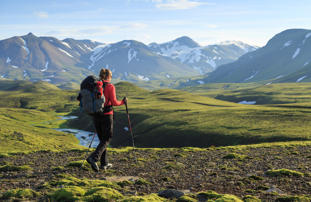 Female hiker with backpack and poles walks into a beautiful landscape of green. Iceland mobile network and coverage.