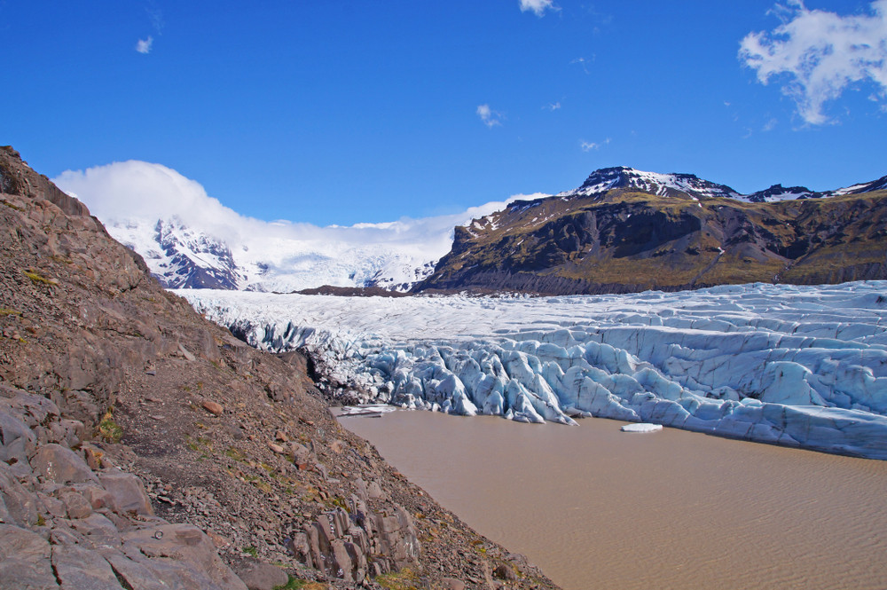 View of a glacier under bright blue skies and rocky surrounds. Skaftafell Nature Reserve just off the Iceland Ring Road.