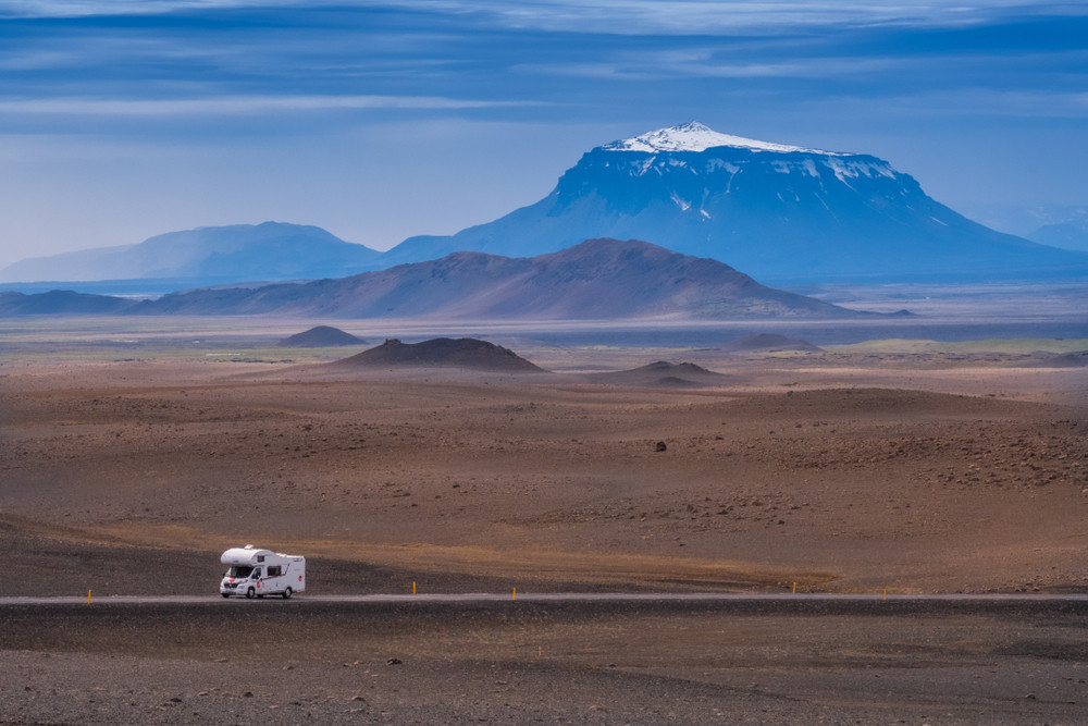 Motorhome driving amidst big landscape of plains and mountains in Iceland.