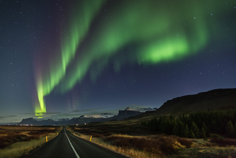 Green Northern Lights in the sky over landscape of mountains and a road. Iceland in October