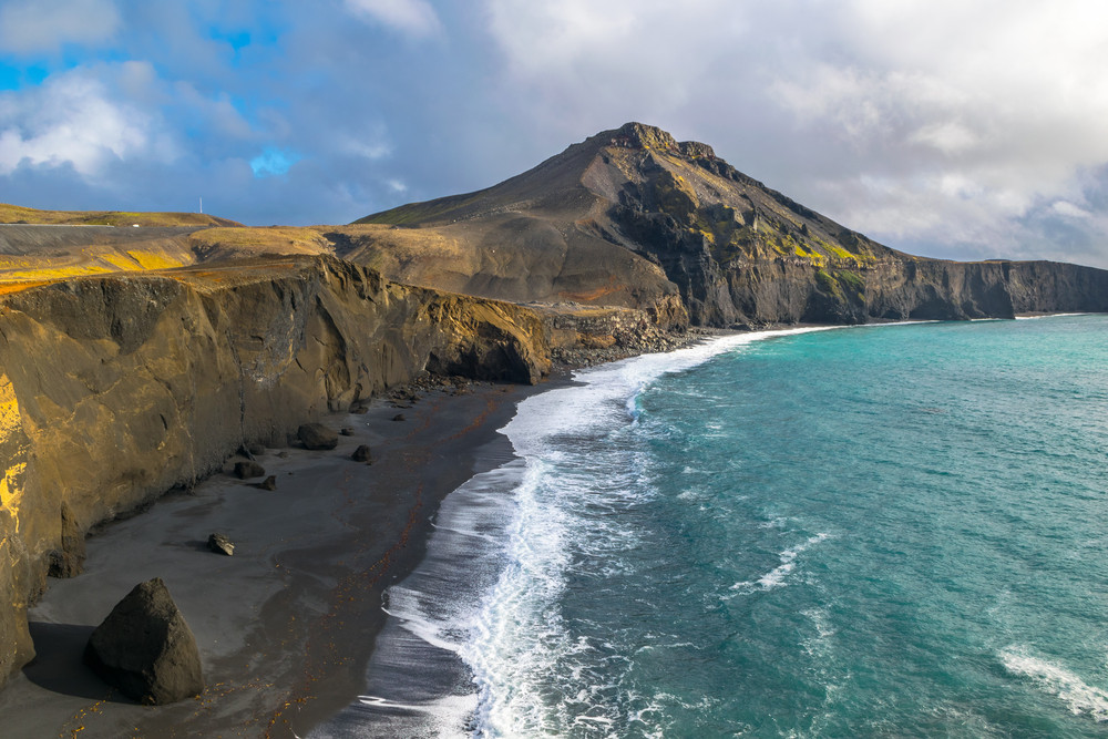 Dramatic cliffs, black sand beach and turquoise sea at Iceland's Reykjanes Peninsula