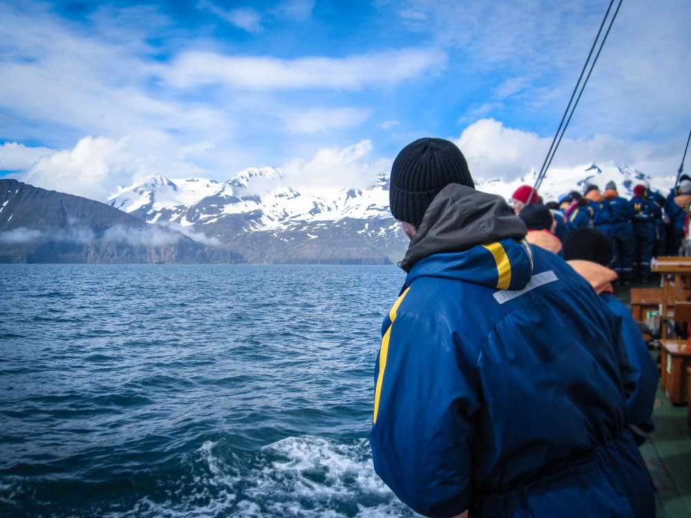 People looking out to sea from a boat with snowy mountains in distance. Iceland Diamond Circle